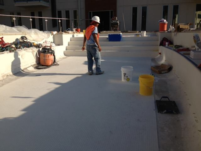 Pool contractors working on tile installation in a swimming pool