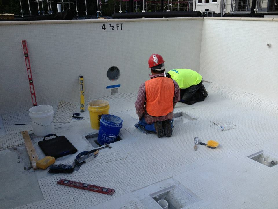 Pool contractors working on pool tile repair