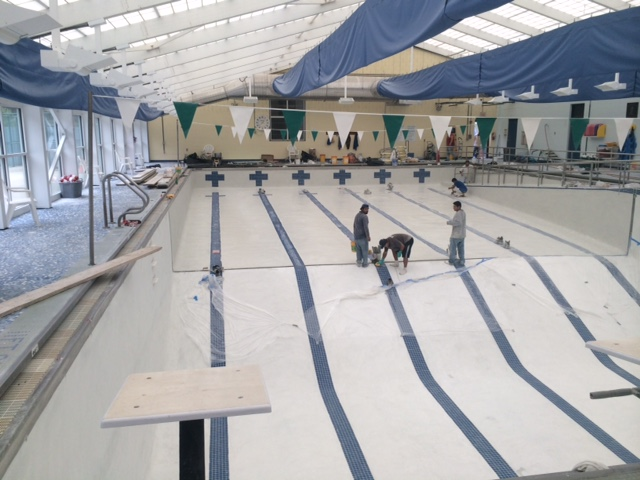 Pool contractors working on pool tile installation
